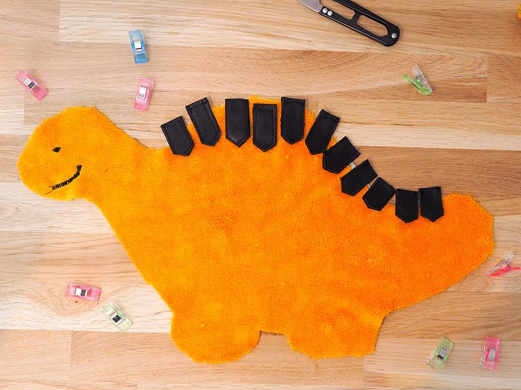 placer les picots cousus sur l'endroit du tissu du dinosaure