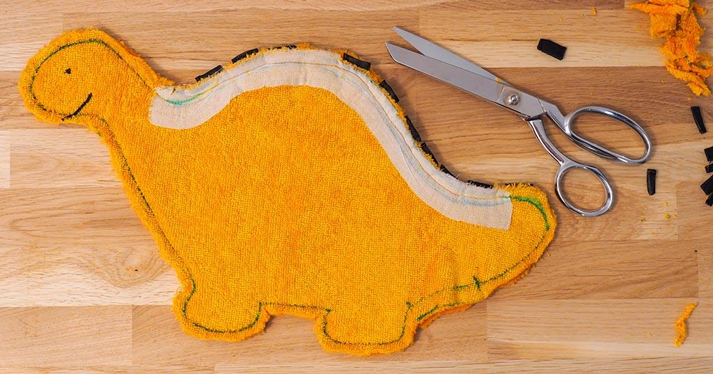 Découper le surplus de tissu du dinosaure cousu